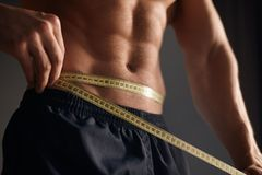 Anonymous sportsman using tape to measure waist. Crop muscular sportsman posing shirtless and measuring waist line with measuring tape Royalty Free Stock Photos