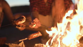Crop people grilling sausages in fire stock footage