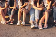 Crop photo of group of young happy tan girls real friends using mobile on sunset background. Crop photo of the group of young happy tan girls real friends using stock image