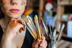 Crop picture of lips and face of beautiful female artist. With purple hair and dirty hands with different paints on them, holding paintbrushes in her art studio royalty free stock photography