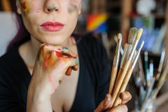 Crop picture of lips and face of beautiful female artist. With purple hair and dirty hands with different paints on them, holding paintbrushes in her art studio royalty free stock photo