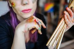 Crop picture of lips and face of beautiful female artist. With purple hair and dirty hands with different paints on them, holding paintbrushes in her art studio stock photography