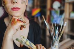 Crop picture of lips and face of beautiful female artist. With purple hair and dirty hands with different paints on them, holding paintbrushes in her art studio royalty free stock image