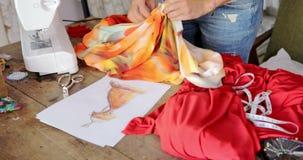 Crop seamstress choosing fabric for dress stock footage