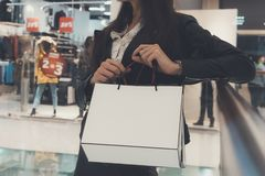 Crop shot of brunette girl holding white paper shopping bags at mall background. Close up of woman's hands holding packages with stock photo