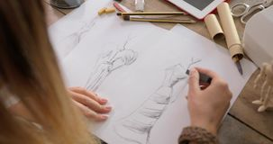Crop shot of dressmaker drawing sketches stock footage