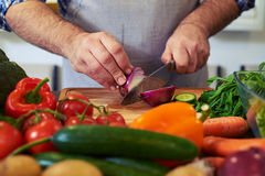Crop shot of hands cutting an onion with a knife. Preparing meal. Hands of a man cutting vegetables in a kitchen. Focus on hands, vegetables lying on the table royalty free stock photography