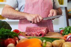 Crop shot of hands sharpening knife for cutting meat royalty free stock photo