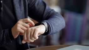 Crop shot of man checking time. Crop shot of male using smartwatch while sitting in cafe. Crop shot of male using smartwatch while sitting in cafe stock video footage