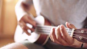 Person playing on ukulele guitar inside. Crop shot of man holding and playing acoustic ukulele guitar sitting inside stock video footage