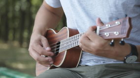 Person playing on little ukulele guitar stock video footage