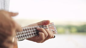Person playing on little ukulele guitar. Crop shot of man holding and playing on little acoustic ukulele guitar sitting in the outdoor park stock video footage