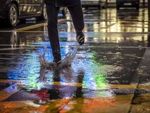 Crop man stepping in puddle on street. Crop shot of man splashing water in puddle on pavement reflecting night city lights Royalty Free Stock Images