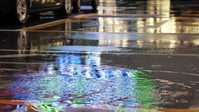Crop of man stepping in puddle on street. Crop shot of man splashing water in puddle on pavement reflecting night city lights. Unrecognizable person passing by stock footage