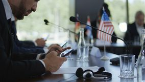 Summit member using phone at table stock footage