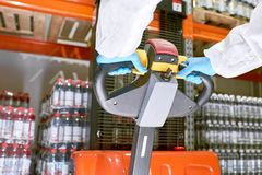 Storage worker pushing handle of pallet truck. Crop sports nutrition production worker hands in protective gloves pushing stacker truck handle in warehouse royalty free stock photo