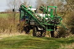 Crop sprayer parked and folded up in field Royalty Free Stock Images