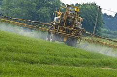 Crop Spraying. Tractor seen from behind spraying crop Stock Photos