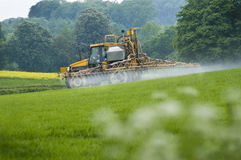 Crop Spraying. Seen from the side tractor crop spraying field of green crop with in the distance other arable fields Royalty Free Stock Photo