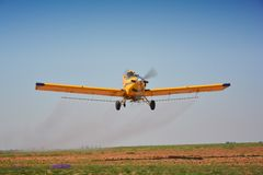 Crop Spraying. Small yellow specialist airplane spraying young maize crops which only recently sprouted, clear blue sky Stock Photo
