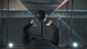 Sportive man working out with weight ball. Crop view from below view of athlete throwing heavy ball up against wall doing hard exercise in gym stock video