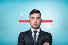 Crop view of a businessman, arms folded, burning dynamite sticks up his ears, on a light-blue background. Have hard day. Work your brain out. Blow your mind stock image