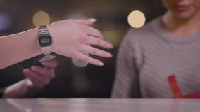 Crop view of customer and server taking payment with machine in cafe stock footage
