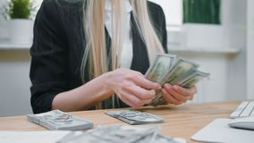 Business woman counting cash in hands. Crop view of female in elegant suit sitting at wooden desk and counting large stock video