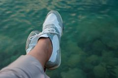 Crop view of female feet on seashore background. Personal point. Of view with relaxing concept and space for text stock photography