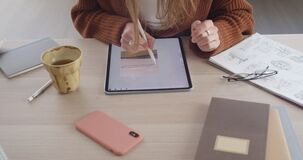 Crop view of female graphic illustrator creating picture while touching tablet screen. Creative designer using digital