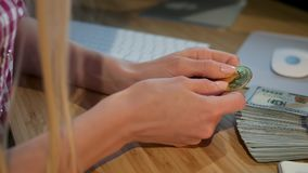Female hands holding bitcoin. Crop view of hands of woman holding shiny metal bitcoin sitting at wooden desk with wad of. Crop view of hands of woman holding stock video footage