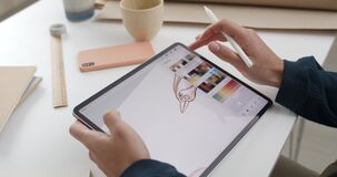 Crop view of illustrator choosing brush color while drawing digital picture. Focus on artist hands using stylus while