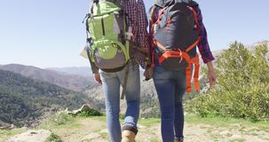 Crop view of loving couple hiking. Crop back view of young people with backpacks holding hands and enjoying view of mountains in summer stock footage