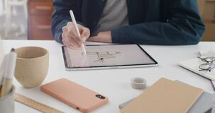 Crop view of male person using stylus while drawing on digital tablet. Graphic illustrator creating picture while