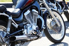 Crop view of motorcicle. Engine, front wheel, exhaust pipe. Shallow focus stock image