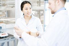 Male scientist showing colleague smartphone. Crop view of standing together during break microbiologists in laboratory smiling, drinking hot beverages and Stock Image
