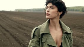 Crop woman in coat. Faceless shot of woman in khaki coat cuddling while standing on ground