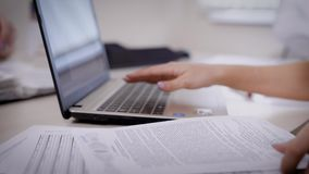Crop woman typing on laptop and reading carefully important paper. Faceless shot of woman looking through information in document and typing on laptop while stock footage
