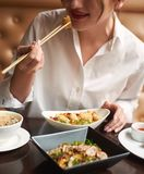 Crop of woman in white ordering meal in Japanese restaurant. Crop of pretty woman in white blouse with red lips ordering meal in luxury Japanese restaurant stock photography