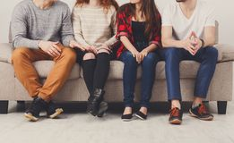 Crop of young friends sitting on couch indoors Royalty Free Stock Photo