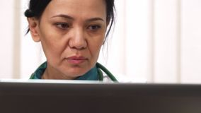 Cropepd se ferment d'un docteur féminin mûr travaillant sur l'ordinateur portable images stock
