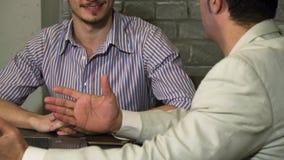 Cropepd a tiré de deux hommes d'affaires parlant au cours de la réunion au bureau clips vidéos