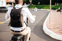 Cropped back view of man with backpack rides on motorbike. Cropped back view of man with backpack rides on modern motorbike outdoors Stock Image