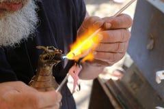 Cropped biały brodaty mężczyzna tworzy szklaną czarodziejkę używa lampworking - topiący szklanych prącia z smok kształtującą gaz  fotografia stock