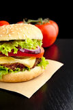 Cropped cheeseburger on paper on wooden black desk Royalty Free Stock Photography