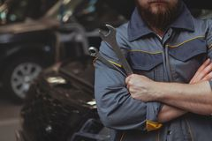 Bearded mechanic working at car service station royalty free stock images