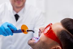 Young man visiting dentist. Cropped close up of a bearded men getting teeth filling done at the dentist office technology ultraviolet lamp tools professionalism Royalty Free Stock Images