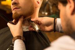 Handsome young bearded man at the barbershop stock photos