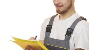 Cropped shot of a industry worker smiling making notes on clipboard. Cropped close up of a bearded repairman in uniform smiling writing on a clipboard isolated stock video