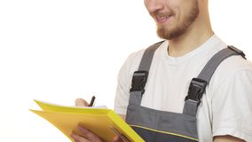 Cropped shot of a industry worker smiling making notes on clipboard. Cropped close up of a bearded repairman in uniform smiling writing on a clipboard isolated Stock Images
